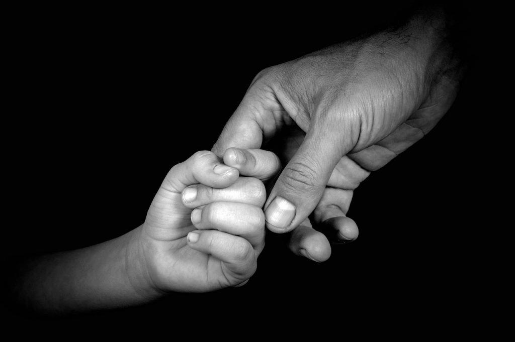 Genitore-che-tiene-mano-del-figlio-durante-la-separazione